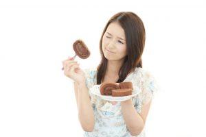 チョコロールケーキを食べたいけど我慢している女性