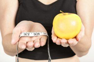 メジャーとリンゴを持っている女性