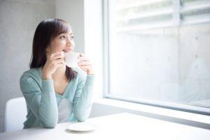 コップをもって窓の外を見ている女性