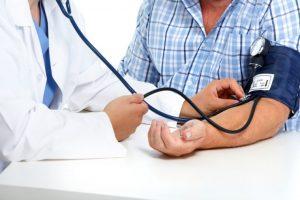 患者の血圧を図っている医者