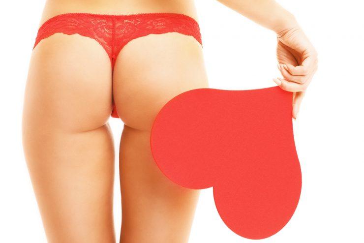 赤いハートをもっている女性の後ろ姿