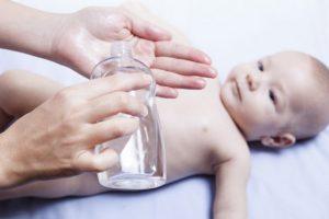 赤ちゃんにベビーオイルを付けようとしている女性
