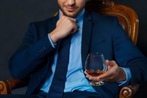 贅沢な椅子に座りワインを片手で持っている