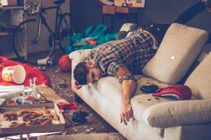 汚い部屋で寝ている男