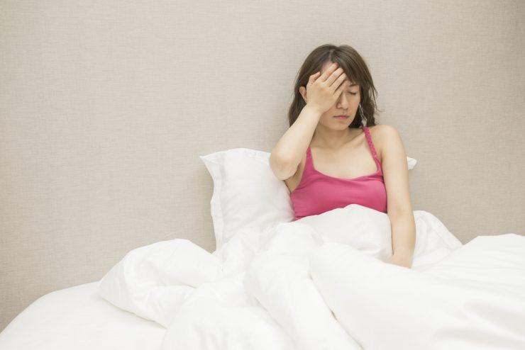 ベッドで頭を抱えている女性