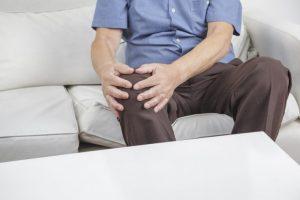 膝を抱えている男性