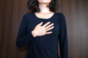 胸を押さえている女性