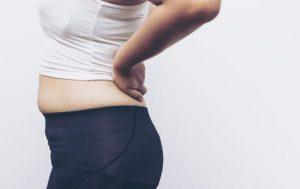 腰を押している太っている女性