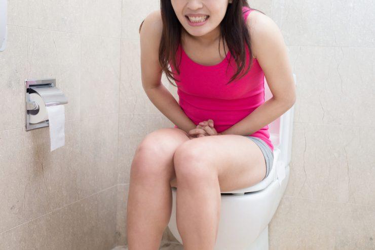ピンクの服を着た女性が便座に座ってお腹を押さえている