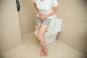 トイレでお腹を両手で押さえている女性