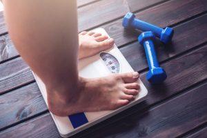 体重計に乗る女性とその前に置かれている青いダンベル