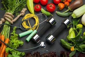 たくさんの野菜の中心に置かれたダンベルと聴診器と縄跳び