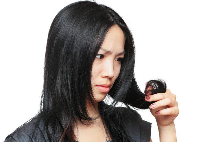 自分の髪を見つめている女性