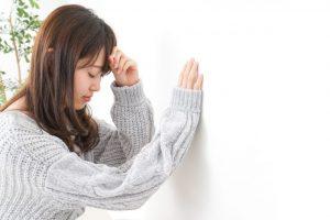 強い頭痛のせいで思わず壁にもたれこむ女性