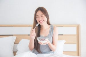 笑顔でシリアルを食べている女性