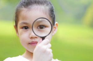 虫眼鏡越しの世界を覗いている少女
