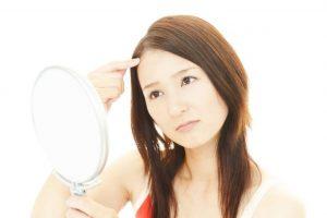 おでこのニキビを手鏡を使って確認している女性