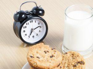 6:14を指している時計とコップに注がれたミルクあとチョコチップクッキー