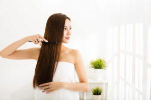 髪をくしで整えている女性