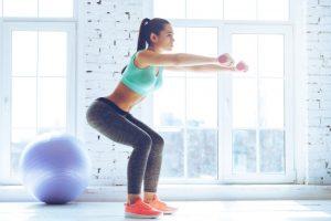 ダンベルを使い運動強度の高いスクワットをしている女性