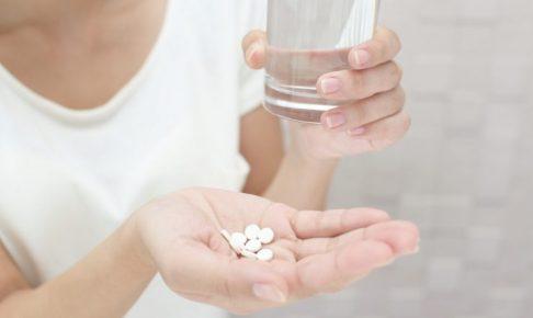 薬とミスのグラスを持っている女性