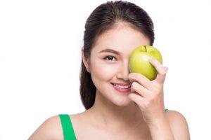 青リンゴで左目を隠している女性