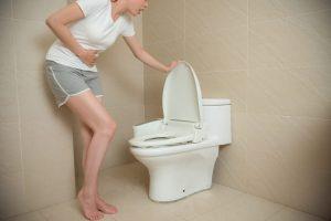 お腹を押さえながらトイレに駆け込んでいる女性