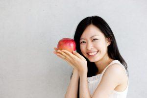リンゴを手に持って笑っている女性