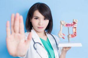 腸の模型を左手に持ち右手を前に突き出している女性医師