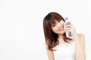ペットボトルに入った水を頬に当てる女性