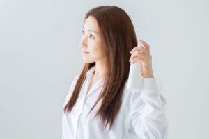 ヘアフレグランスを髪にスプレーをしている女性