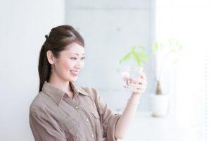 鉢に入っている植物を見ている女性