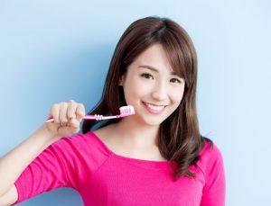 ピンク色の歯ブラシを持った女性
