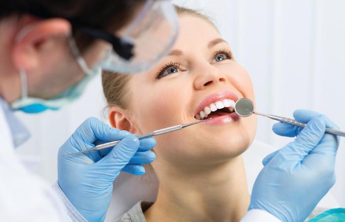歯の検査を受けながら笑っている女性