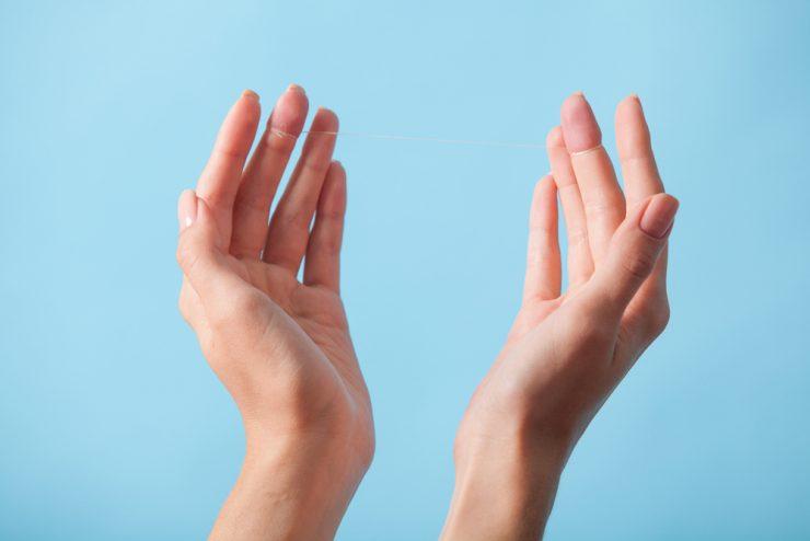 デンタルフロスが両手の中指にまかれている