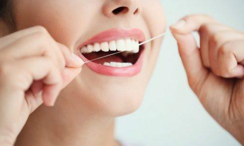 デンタルフロスを歯に入れている女性の半顔