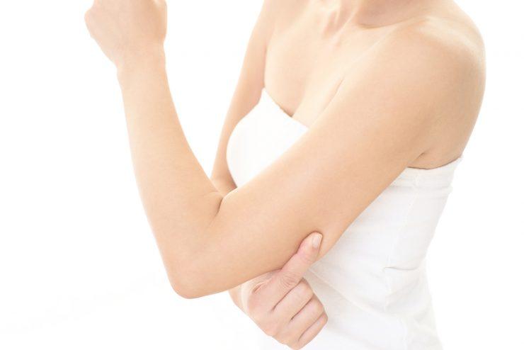 二の腕をつんでいる女性