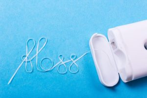 糸型のデンタルフロスがFLOSSの字を描いている写真