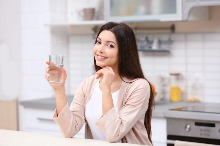 水のコップを持って笑っている女性