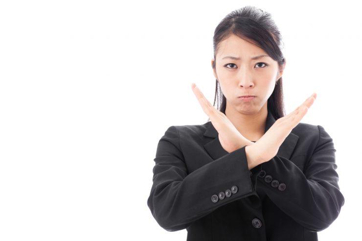 両手をバツの合図をしている女性