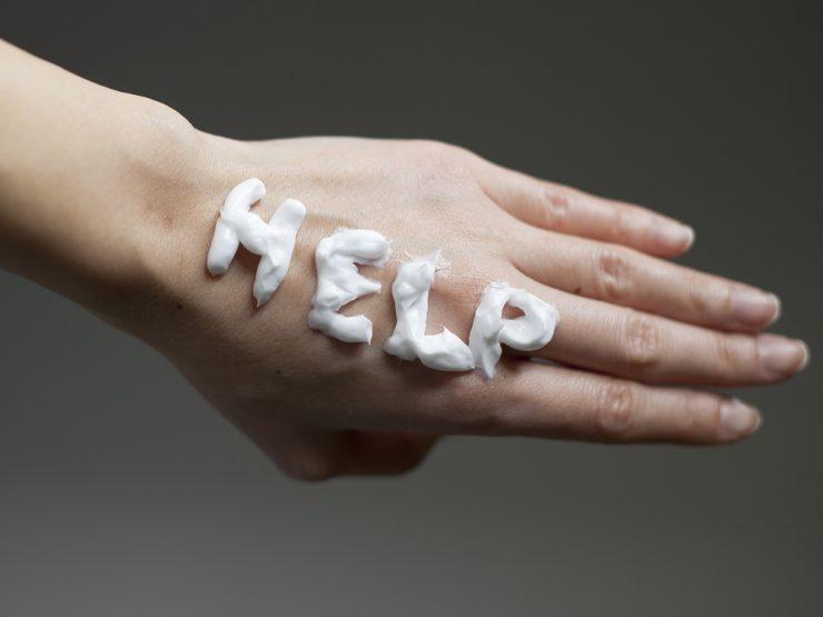 手にクリームでヘルプの字を書いている