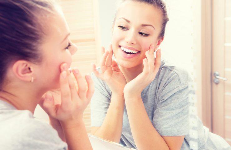 鏡を見ながら笑っている女性