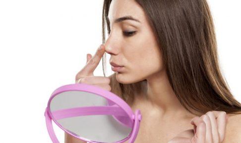 鏡で顔を見ている女性