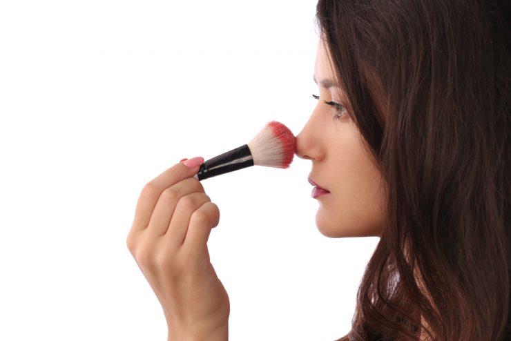 化粧ぶらしを鼻に当てている女性