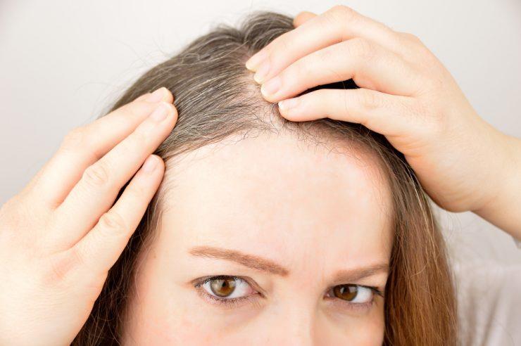 自分の頭皮を見ている女性