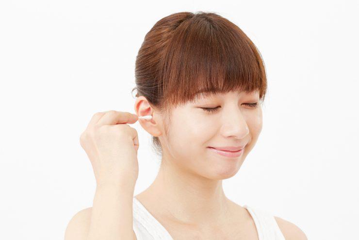 綿棒で耳をきれいにする女性