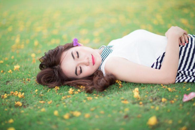 芝生の上で寝ている女性