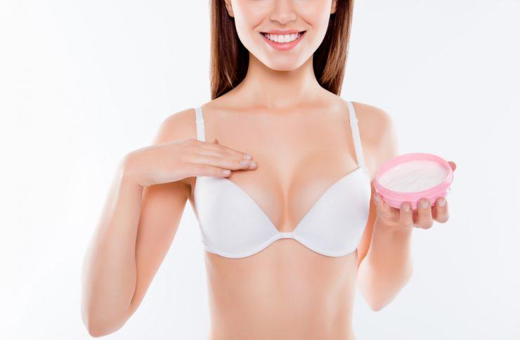 胸にクリームを塗っている女性