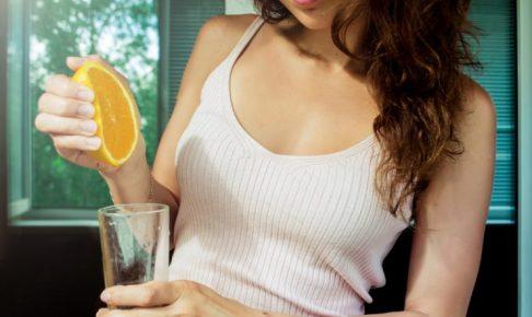 オレンジを絞っている女性