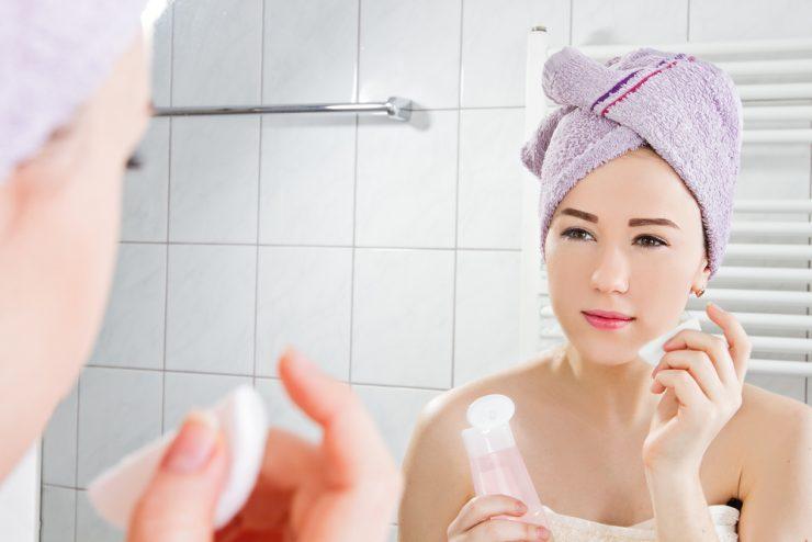 鏡を見て化粧水をつけている女子
